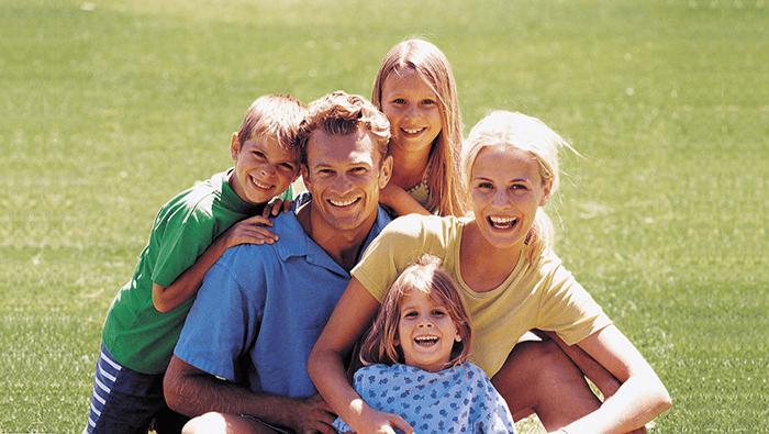 Счастливая семья сидит на поле