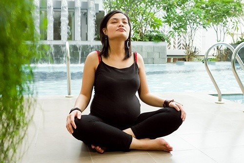 """Беременная женщина сидит в позе """"Лотоса"""""""