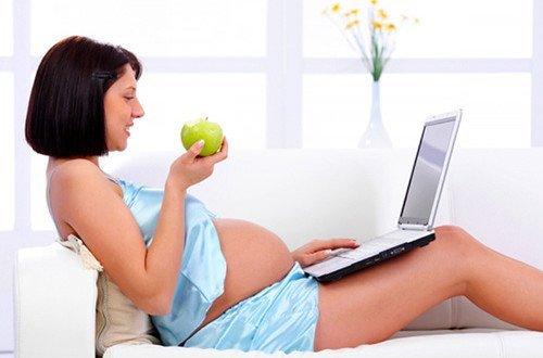 Беременная женщина за ноутбуком