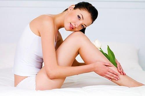 Девушка гладит свои ноги - Эпиляция - советы и уход за кожей