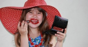 Девочка в шляпе красит губы