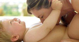 Мама целует малышу животик