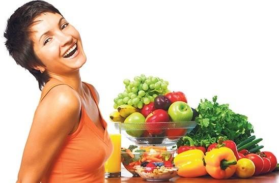 Женщина ест фрукты и овощи