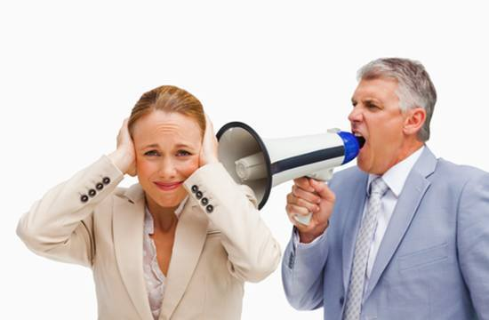 Мужчина кричит в мегафон около уха женщины пытающейся закрыть уши руками