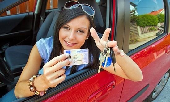 Девушка в машине показывает удостоверение водителя