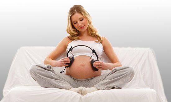 Беременная женщина с наушниками у живота