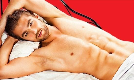 Полуобнаженный мужчина лежит на кровати