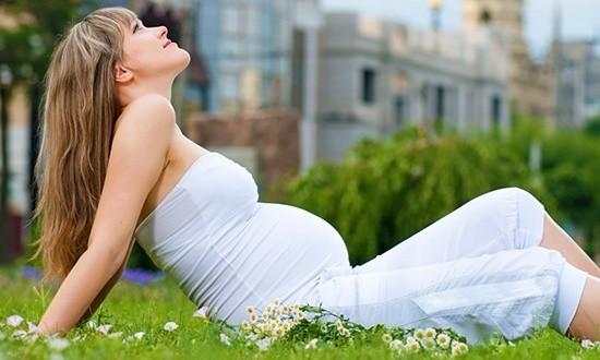 Беременная счастливая женщина сидит на траве с ромашками