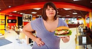 Девушка держится за живот в ресторане фаст фуд