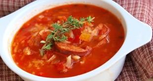 Тарелка чечевичного супа с томатами и колбасками на салфетке