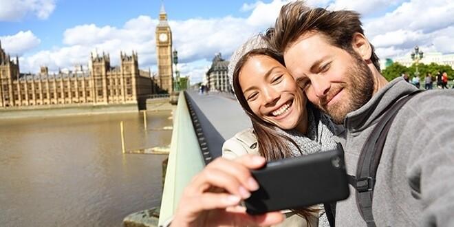 Парень с девушкой в Лондоне на набережной делают селфи