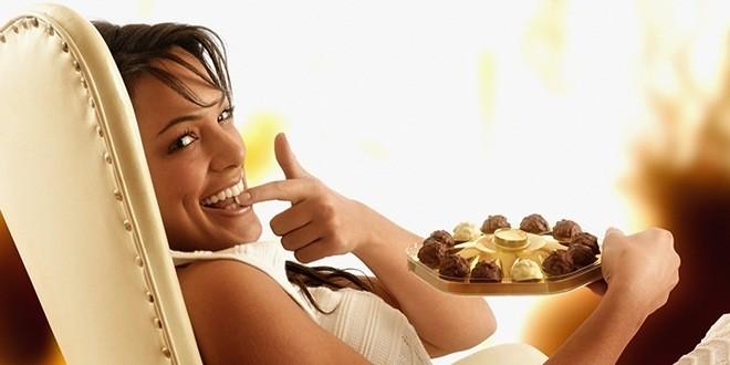 Женщина ест шоколадные конфеты