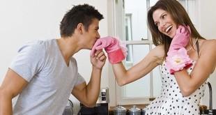 Мужчина целует руку женщины в резиновых перчатках на кухне