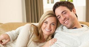 Счастливые мужчина и женщина сидят на диване