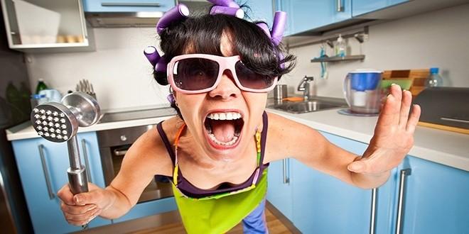 Нервная женщина на кухне с молотком для отбивания мяса