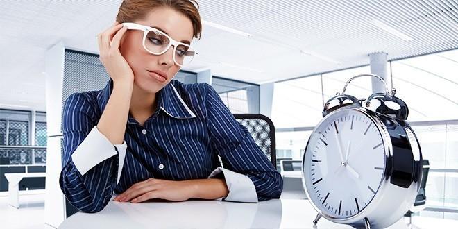 Женщина в офисе с часами сидит за столом