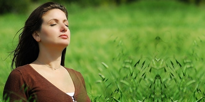 Женщина дышит на зеленом поле