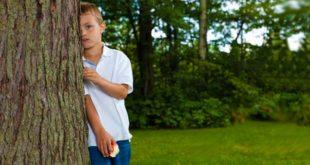 Мальчик выглядывает из за дерева