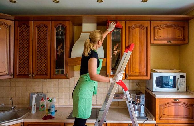 Женщина на кухне на стремянке