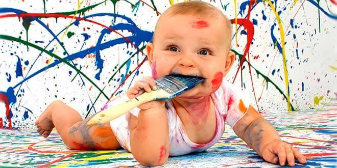 Малыш лежит на животе весь в краске