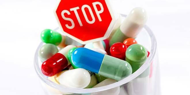 Таблетки в стакане и знак стоп