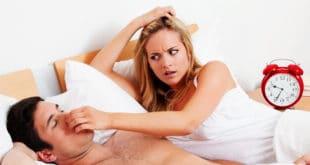 Женщина затыкает нос храпящему мужчине