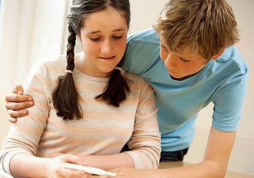 Мальчик и девочка смотрят тест на беременность
