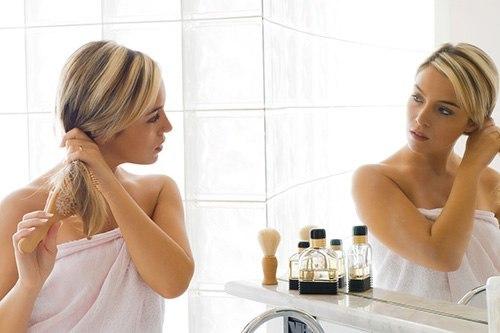 Женщина у зеркала причесывается