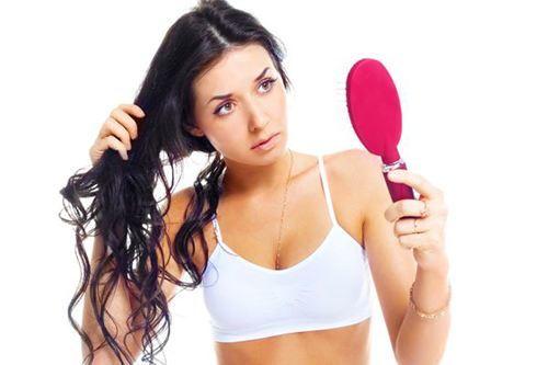 Девушка смотрит в зеркало на волосы