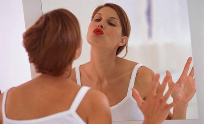 Женщина целует свое отражение в зеркале