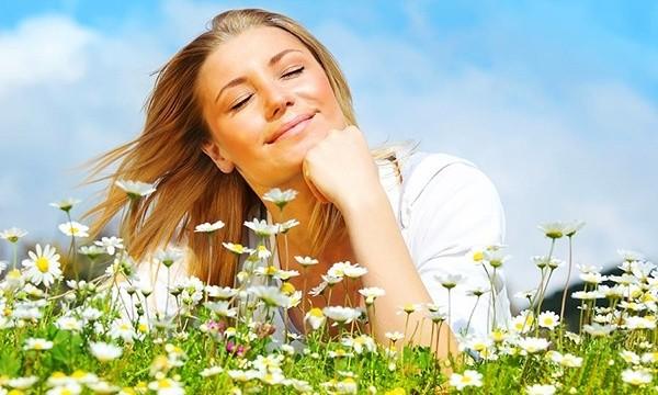 Счастливая женщина лежит на лугу ромашек