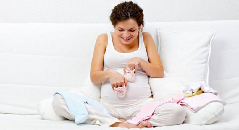 Беременная женщина играет с пинетками