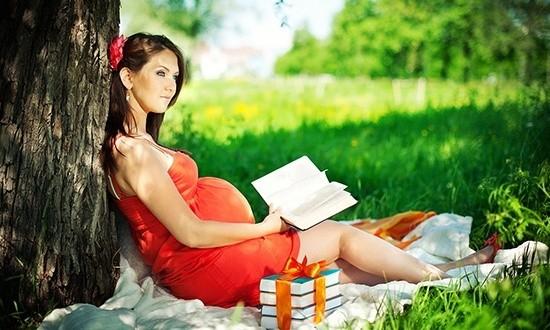 Беременная женщина читает книгу на природе