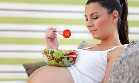 Беременная женщина ест салат
