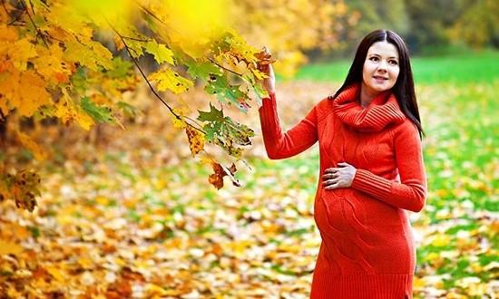 Беременная женщина в красном платье в осеннем парке