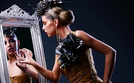 Женщина смотрит на свое отражение в зеркале