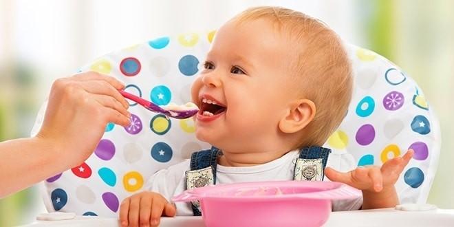 Счастливый ребенок ест на стульчике