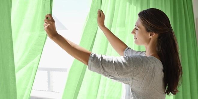 Женщина зашторивает окно зелеными шторами