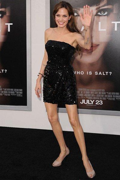 Анджелина Джоли в черном платье стоит