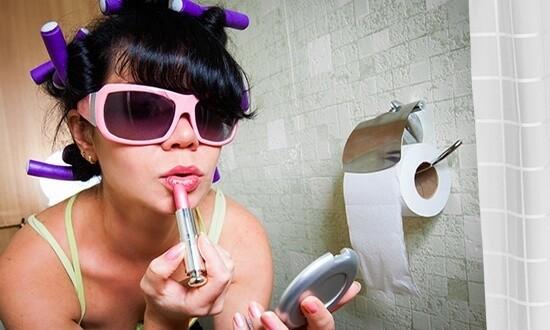 Женщина в очках в туалете красит губы