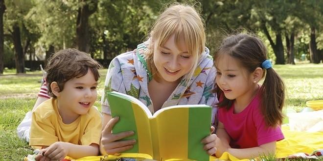 Мама на поляне читает своим детям книгу