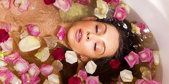 Женщина лежит в ванной с лепестками роз