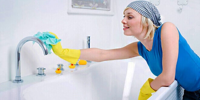 Женщина убирается в ванной комнате