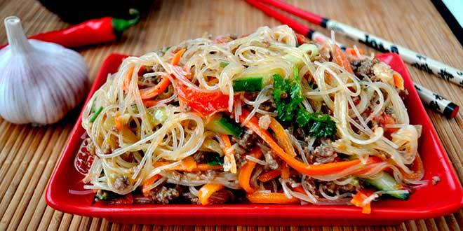 Салат с лапшой и овощами в красной тарелке