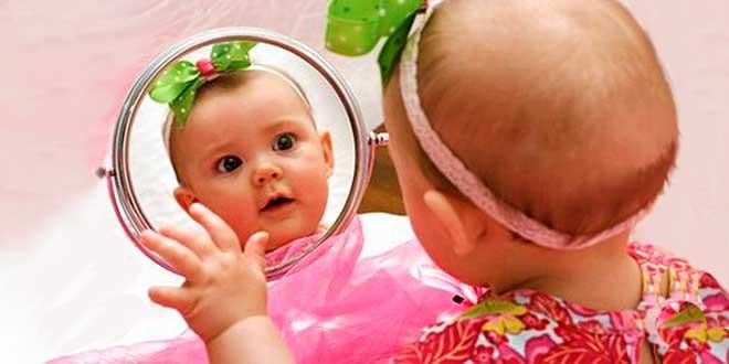 Маленькая девочка смотрится в зеркало