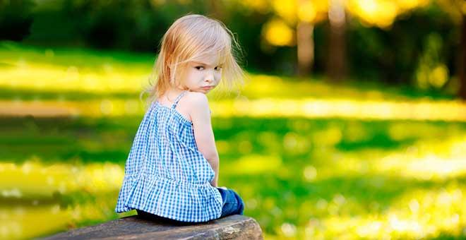 Девочка сидит на скамейке