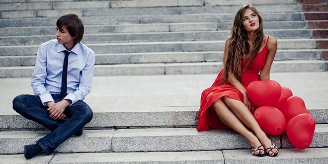 Девушка в красном и мужчина сидят на ступенях