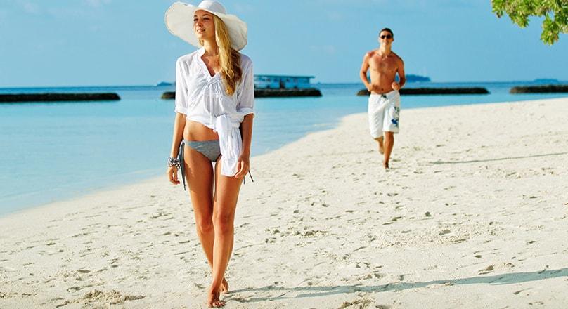Девушка в шляпе идет по пляжу