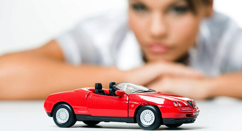 Девушка смотрит на игрушечную машинку