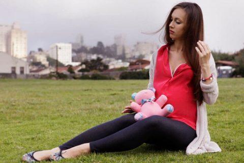 Беременная женщина сидит на траве